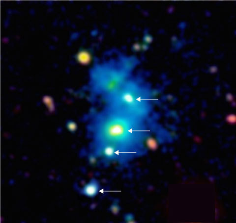 Image of the region of the space occupied by the rare quasar quartet. The four quasars are indicated by arrows. The quasars are embedded in a giant nebula of cool dense gas visible in the image as a blue haze. The nebula has an extent of one million light-years across, and these objects are so distant that their light has taken nearly 10 billion years to reach telescopes on Earth. This false color image is based on observations with the Keck 10m telescope on the summit of Maunakea in Hawaii.