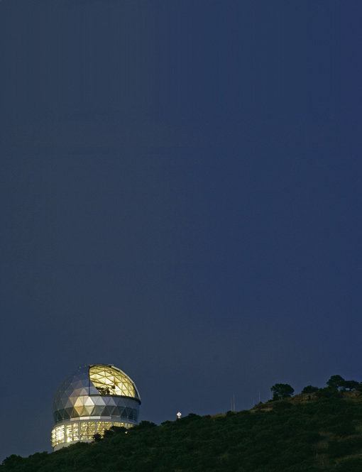 Figure 3: The Hobby-Eberly Telescope gleams in silver and gold against a deep blue night sky. This telescope, located at McDonald Observatory in Texas, was used for the survey of 700 galaxies that formed the first step of the systematic search by van den Bosch and his colleagues for the most massive galactic black holes.