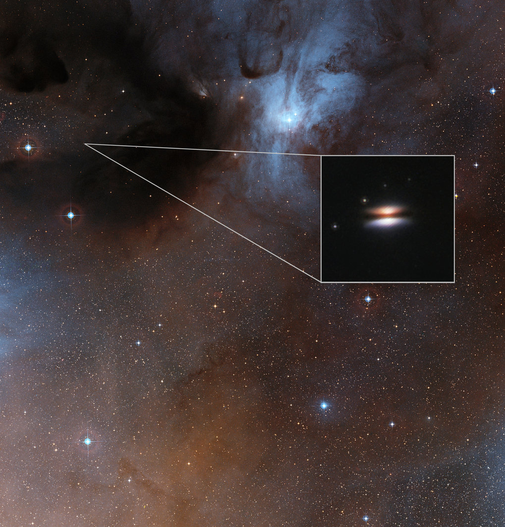 <p>The Rho Ophiuchus star formation region at a distance of about 400 light-years from Earth. The inset shows an infrared image of the Flying Saucer protoplanetary disk, taken with the Hubble Space Telescope. Recent observations of this disk have revealed dust in that disk to have an unexpectedly low temperature.</p>